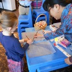 Eagle Chapter faculty adviser, Hong Zhan, shows a little girl how to write Chinese characters