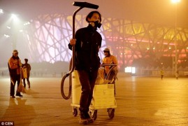 Brother Nut walks around Beijing sucking up air pollution into a vacuum.