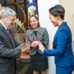 Team Pengyou Intern Melodie Ha hands Ambassador Branstad his name tag.