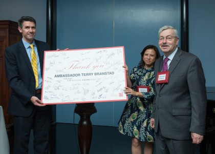 Travis Tanner, President of The US-China Strong Foundation & Holly Chang, Founder of Project Pengyou, present Ambassador Branstad with a signed gift from all the guests.
