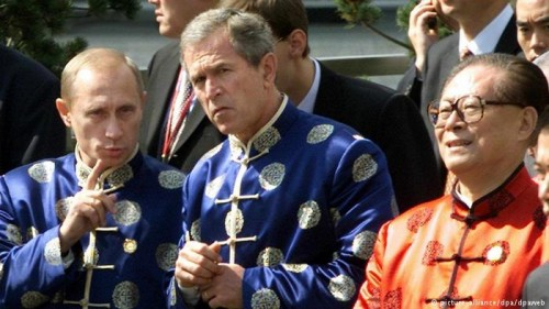 Presidents Vladimir Putin, George W. Bush, and Jiang Zemin wear silk jackets as a symbol of friendship during the 2001 APEC summit. Image credit: Picture alliance/ dpa/ dpaweb